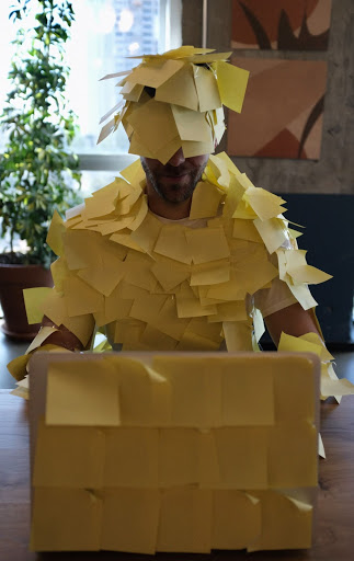 a man covered in post-it notes, reminding him of his tasks for the day